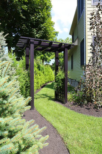 Vine covered pergola with sod lawn and mulch in Laurel Hollow