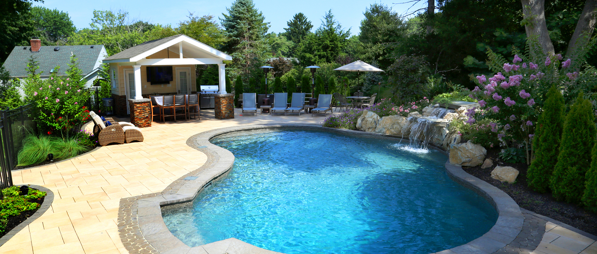 Natural pool with paver patio cabana and outdoor TV and stone kitchen in Sands Point