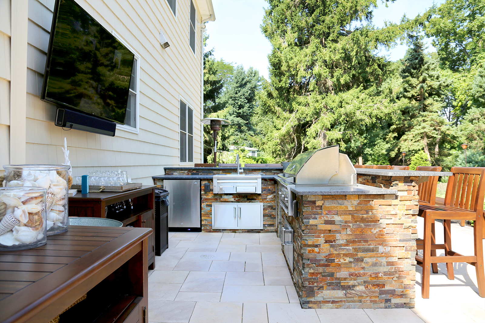 Outdoor television and stone kitchen with outdoor wet bar in Sands Point