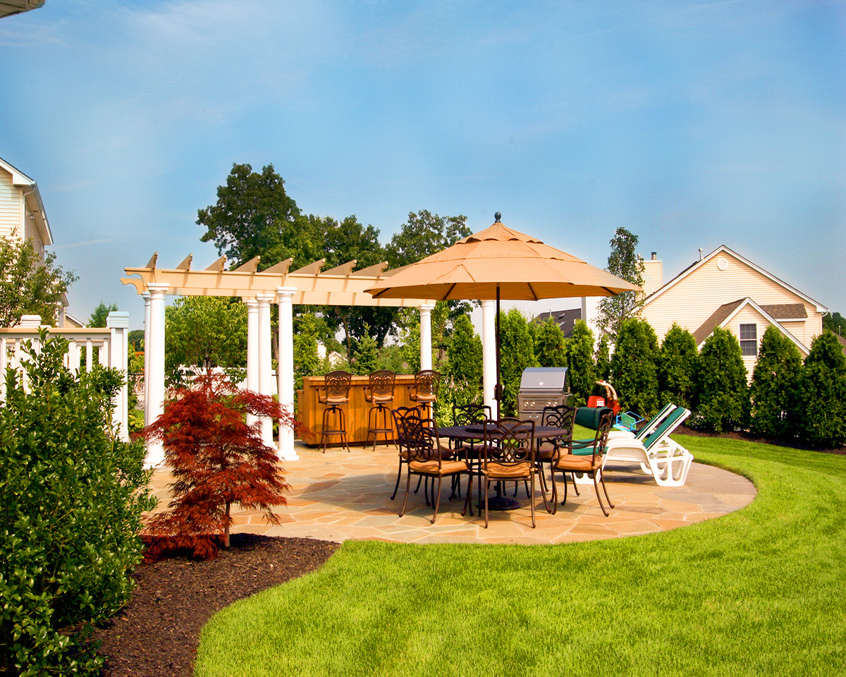 Bluestone patio with pergola and exotic planting and outdoor bar in Muttontown