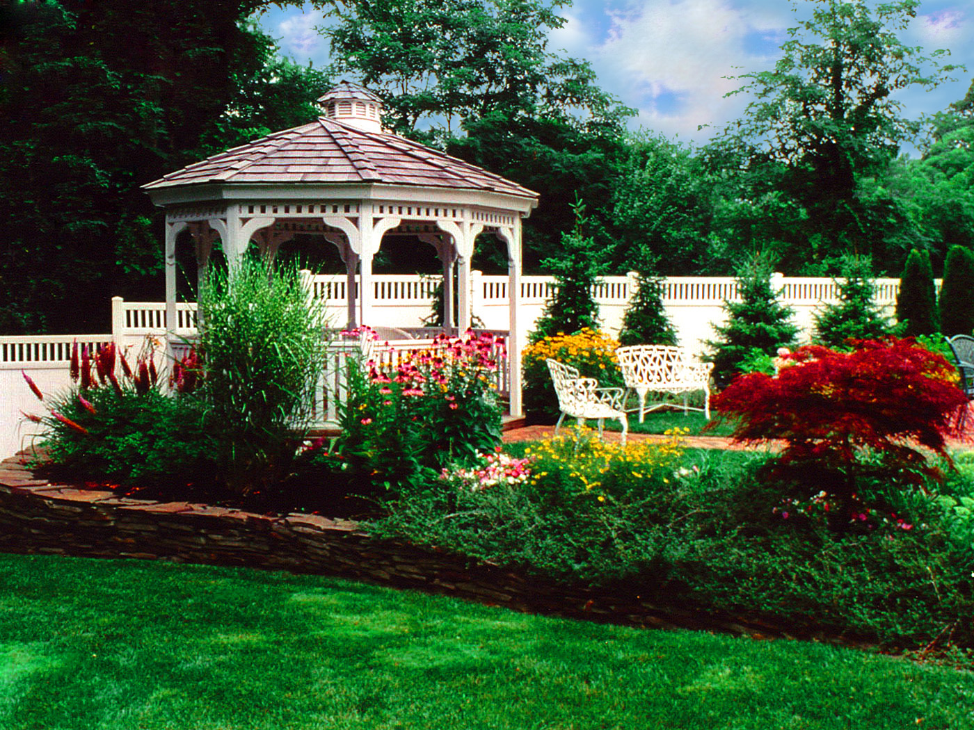 Gazebo with blue stone retaining wall and brick walkway in West Hampton
