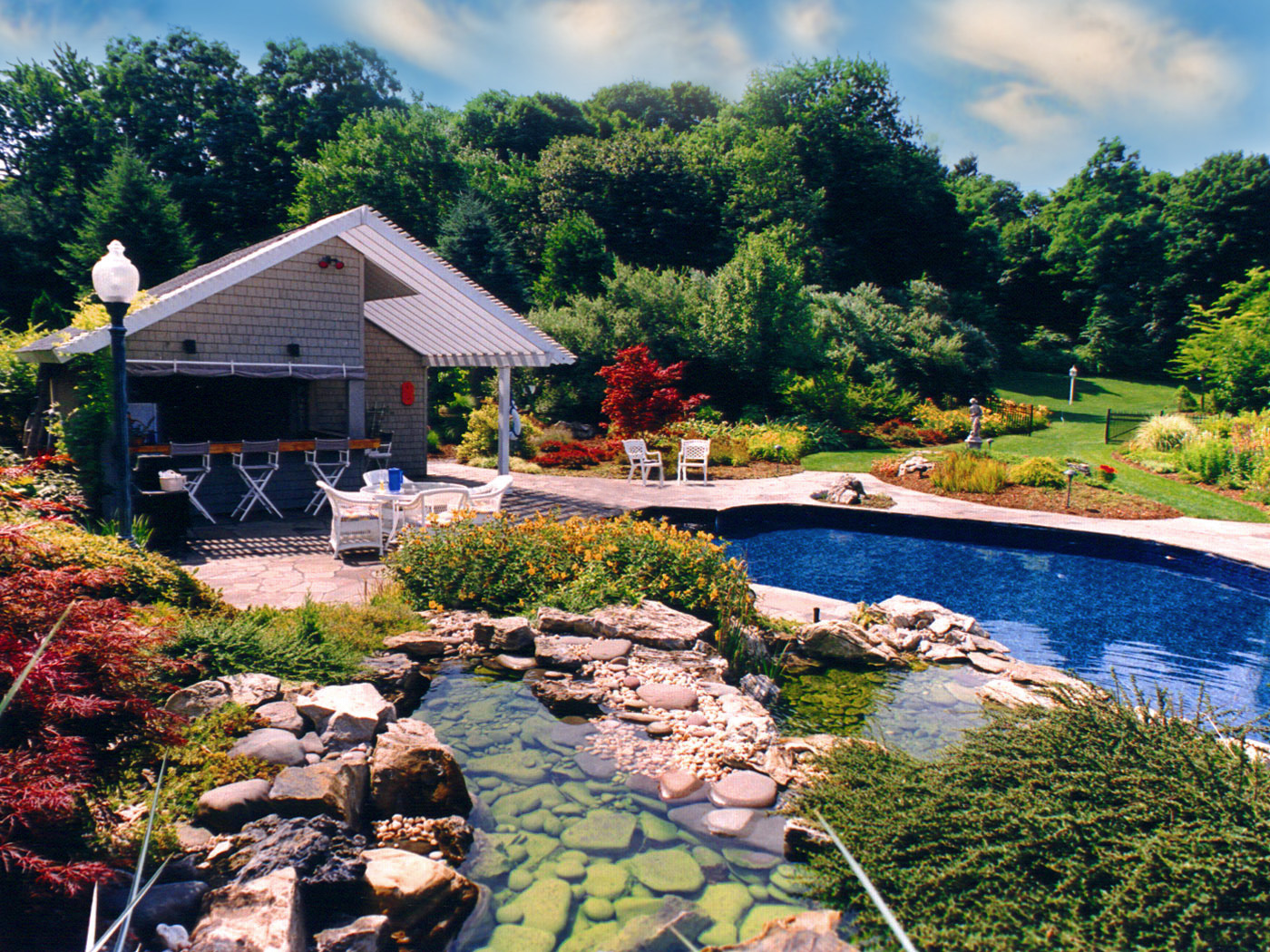 Cabana and natural pool with waterfall on stone patio  landscapers near me in Brookville