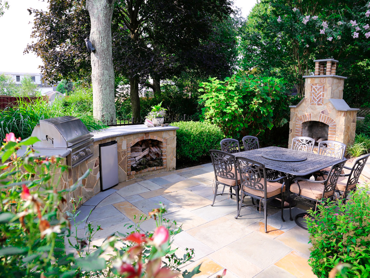 Outdoor kitchen with blue stone patio and outdoor stone fireplace in Dix Hills