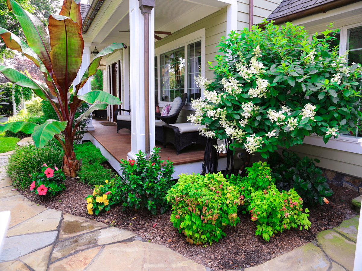 Front yard porch and walk way with bluestone and exotic colorful plants in Dix Hills
