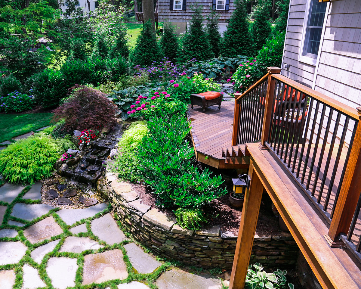 Bluestone patio colorful privacy planting and mahogany deck in Huntington