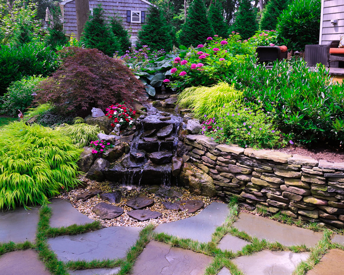 Stone retaining wall with waterfall  landscapers near me in Sands point