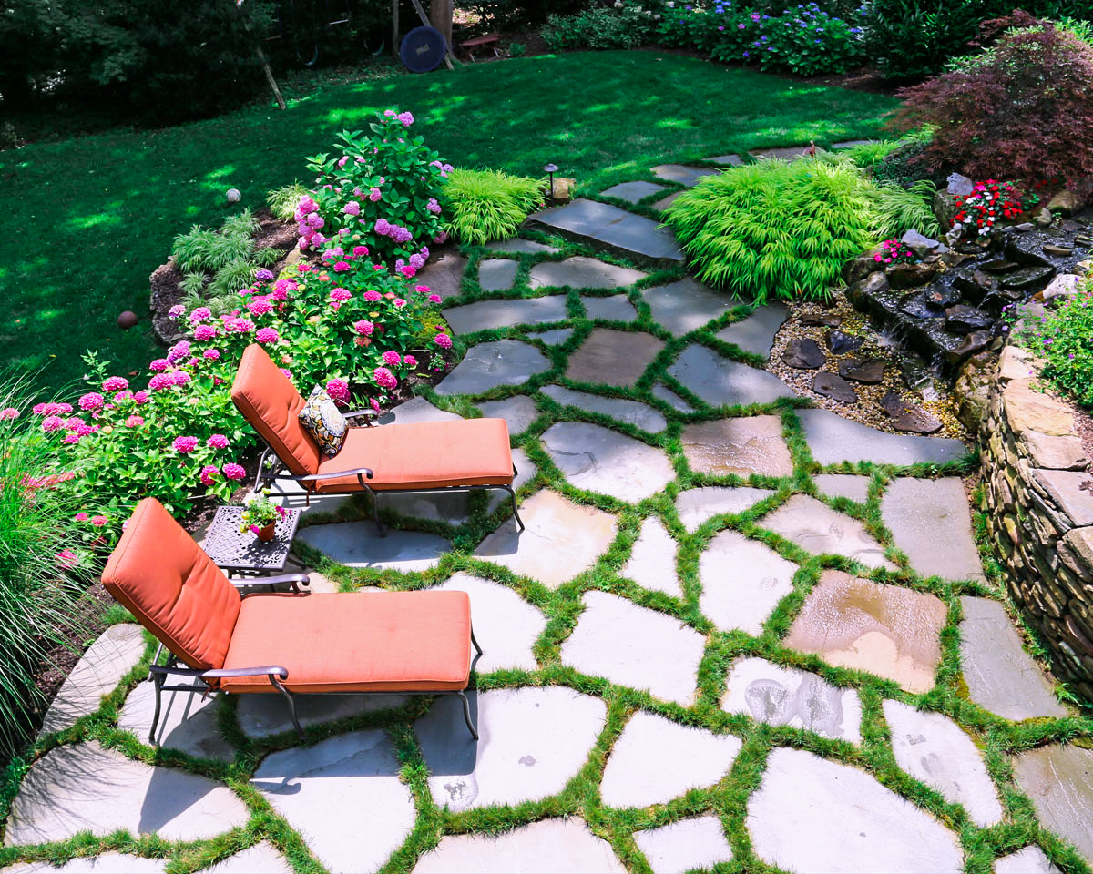 Natural stone patio and back yard lounge with landscapers near me in Brookville