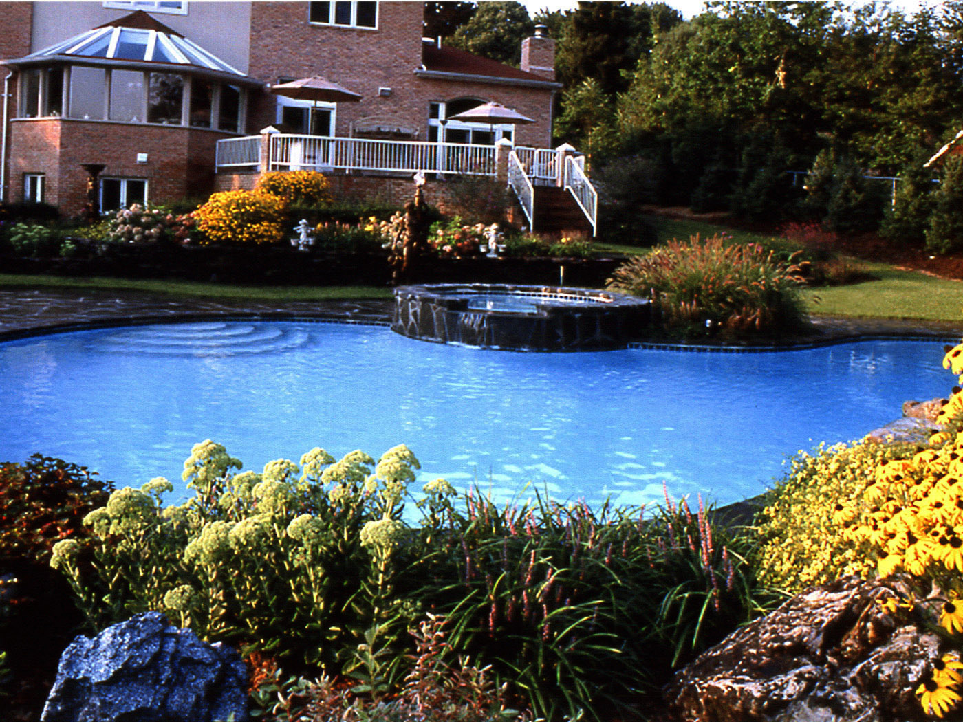 Stone pool jacuzzi and waterfall with beautiful planting in Brookville.