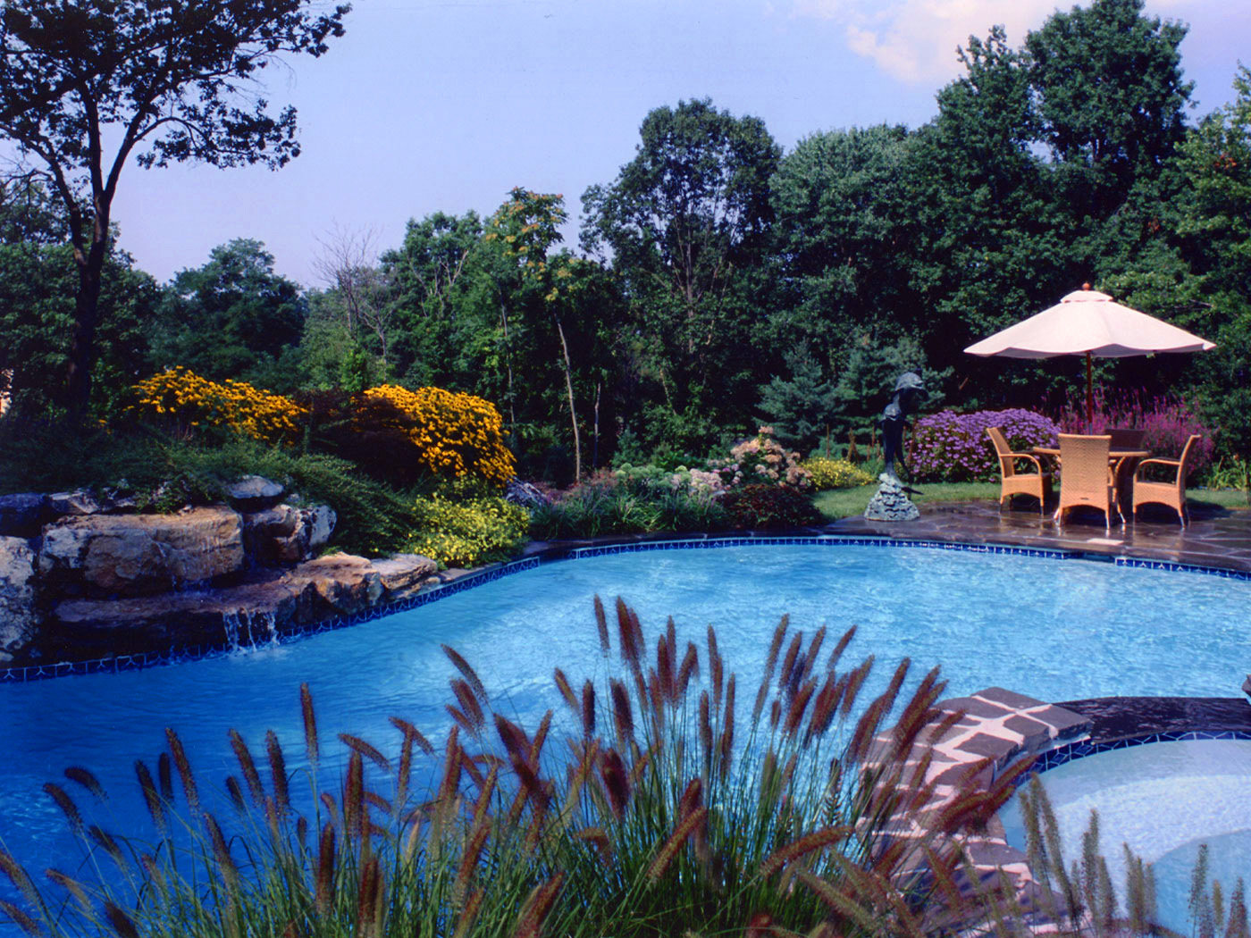 Naturalistic pool and waterfall with stone work and exotic planting in Upper Brookville