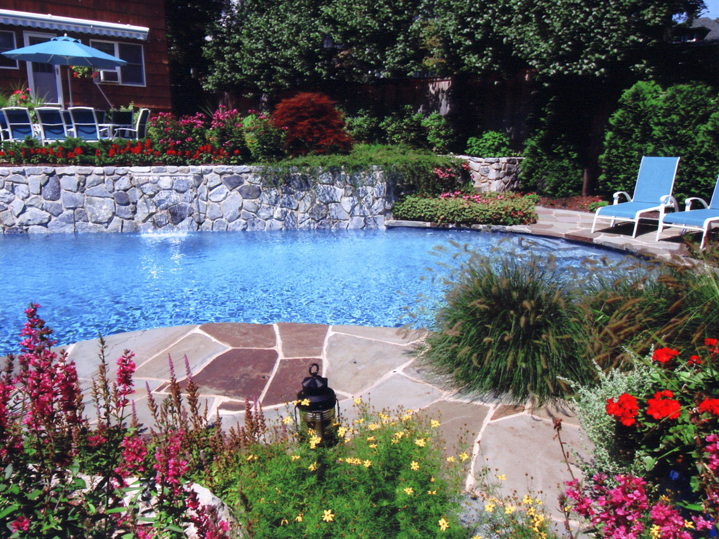 Bluestone walkway with stone retaining walls waterfall and pool in Dix Hills