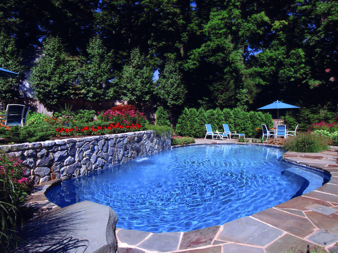 Natural pool and waterfall with colorful plants and diving board in Upper Brookville