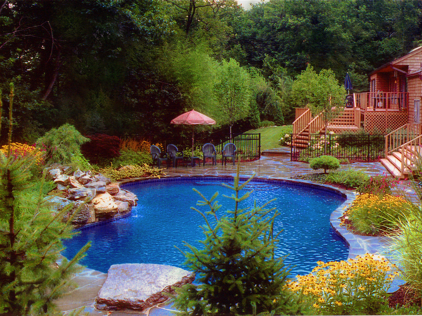 Pond like pool with stonework with stone patio pool cabana and waterfall in Huntington